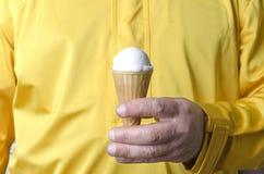 Hombre que lleva la ropa amarilla y que sostiene el cono de helado blanco sabroso Helado en cono de la galleta foto de archivo