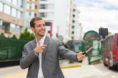 Hombre que lleva la ropa formal que presenta con el selfie Imagenes de archivo