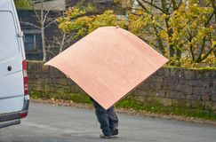 Hombre que lleva las hojas de madera grandes Fotos de archivo