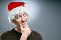 Hombre que lleva los regalos de Santa Hat Thinking Of What para dar Imágenes de archivo libres de regalías