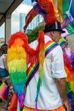 Hombre que lleva a Pride Parade Wings con el arco iris de LGBT Foto de archivo libre de regalías