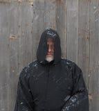 Hombre que lleva un cabo encapuchado negro con la nieve que cae abajo Imagenes de archivo