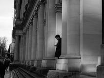 Hombre que manda un SMS en ciudad en el teléfono móvil en blanco y negro Imagen de archivo
