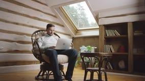 Hombre que manda un SMS en el ordenador portátil en el ático metrajes