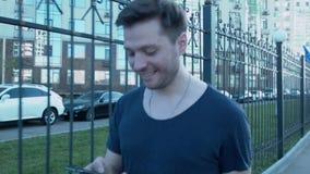 Hombre que manda un SMS en el teléfono Empresario profesional urbano casual que usa el edificio de oficinas exterior feliz sonrie metrajes