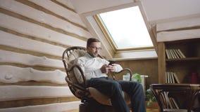 Hombre que manda un SMS en el teléfono móvil en el ático metrajes