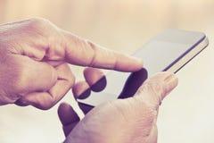 Hombre que manda un SMS en su smartphone Fotos de archivo libres de regalías