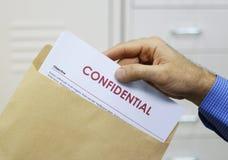 Hombre que maneja documentos confidenciales Fotografía de archivo libre de regalías