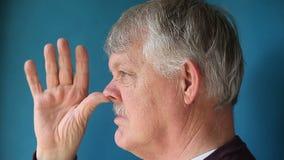 Hombre que manosea la nariz con los dedos almacen de video