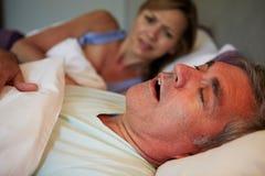 Hombre que mantiene a la mujer despierta cama con roncar Foto de archivo libre de regalías