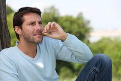 Hombre que mastica la lámina de la hierba foto de archivo libre de regalías