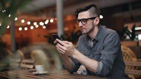 Hombre que mecanografía algo en Smartphone metrajes
