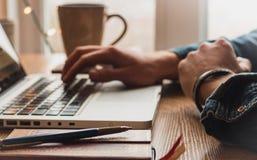 Hombre que mecanografía en el ordenador portátil con el lápiz, la taza de café y la libreta foto de archivo