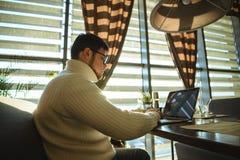 Hombre que mecanografía en el ordenador portátil en caffe Fotos de archivo