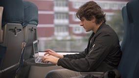Hombre que mecanografía en el ordenador portátil en el tren almacen de metraje de vídeo