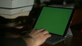 Hombre que mecanografía en la tableta Pantalla verde para su contenido de encargo de la pantalla