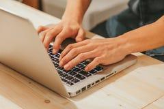 Hombre que mecanografía en un ordenador portátil moderno Imágenes de archivo libres de regalías
