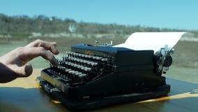 Hombre que mecanografía en una máquina de escribir vieja con sus manos en el aire abierto metrajes