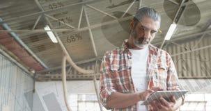 Hombre que mecanografía en una tableta en un almacén 4k almacen de metraje de vídeo