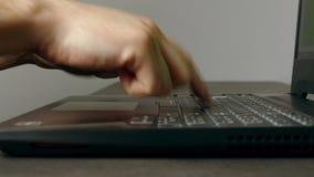 Hombre que mecanografía muy lento en el teclado del ordenador portátil almacen de metraje de vídeo