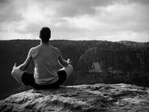 Hombre que medita en Lotus Pose en el acantilado rocoso Yoga practicante del deportista en el borde de piedra Imágenes de archivo libres de regalías