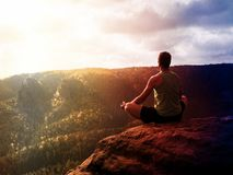 Hombre que medita en Lotus Pose en el acantilado rocoso Yoga practicante del deportista en pico Fotos de archivo libres de regalías