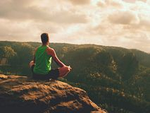 Hombre que medita en Lotus Pose en el acantilado rocoso Yoga practicante del deportista en el borde de piedra Fotografía de archivo