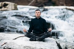 Hombre que medita en Lotus Pose en la cascada Imagen de archivo