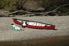 Hombre que miente al lado de la canoa Foto de archivo