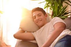 Hombre que miente comfortablemente en el sofá Fotografía de archivo