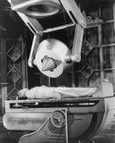 Hombre que miente debajo de la máquina enorme (todas las personas representadas no son vivas más largo y ningún estado existe Gar Foto de archivo