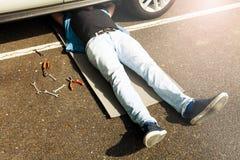 Hombre que miente debajo de la parte de abajo auto que hace el trabajo de la reparación Foto de archivo