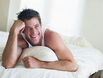 Hombre que miente en cama Fotos de archivo