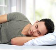 Hombre que miente en dormir de la cama Fotos de archivo libres de regalías