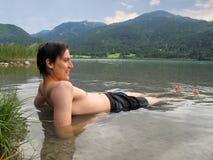 Hombre que miente en el lago y la sonrisa Imagen de archivo libre de regalías