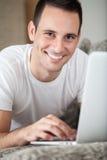 Hombre que miente en el sofá con el ordenador portátil Imagenes de archivo
