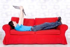 Hombre que miente en el sofá con la computadora portátil Imágenes de archivo libres de regalías