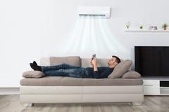 Hombre que miente en el sofá debajo del acondicionador de aire usando la tableta imagenes de archivo