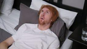 Hombre que miente en la cama que siente incómoda, malestar fotografía de archivo