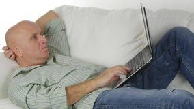 Hombre que miente en la comunicación inalámbrica del ordenador portátil del uso del sofá foto de archivo libre de regalías