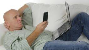 Hombre que miente en la comunicación inalámbrica del teléfono móvil y del ordenador portátil del uso del sofá fotos de archivo libres de regalías