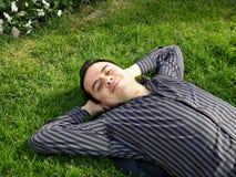 Hombre que miente en la hierba Fotografía de archivo libre de regalías