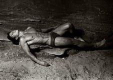 Hombre que miente en la playa Imagenes de archivo