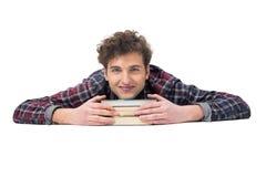 Hombre que miente en la tabla con los libros Foto de archivo libre de regalías