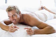 Hombre que miente en señalar de la cama Imagenes de archivo