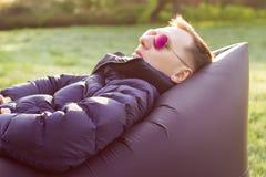 Hombre que miente en un sofá inflable Foto de archivo