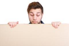 Hombre que mira abajo en muestra en blanco del cartel Imagen de archivo libre de regalías