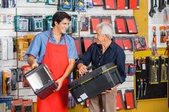 Hombre que mira al vendedor While Selecting Toolbox Fotografía de archivo libre de regalías