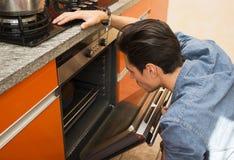 Hombre que mira algo cocinar en el horno Fotos de archivo libres de regalías
