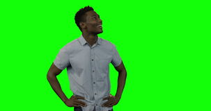 Hombre que mira alrededor contra la pantalla verde almacen de video